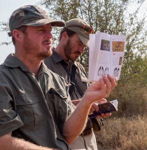 Colin illustreert een en ander met het sporenboek terwijl Cobus aandachtig meeleest
